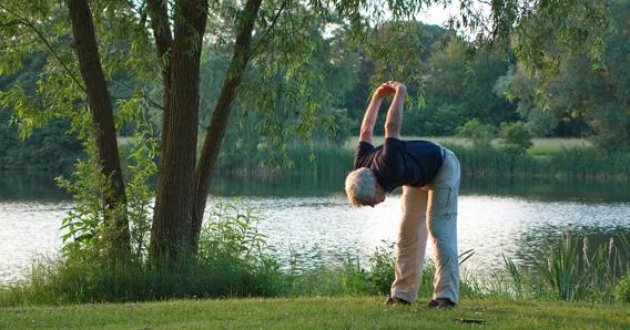 starszy mężczyzna ćwiczączy w parku