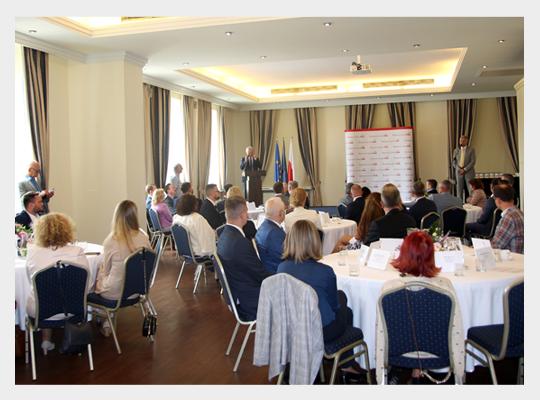 Publiczność konkursu BCC siedząca przy stolikach podczas przemówienia jednego z organizatorów