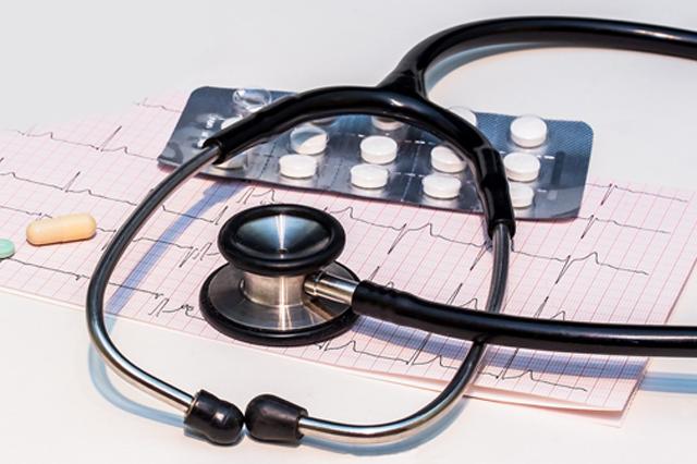 Stetoskop na wydruku kardiogramu oraz blister leków