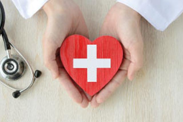 Ręce lekarza trzymającego drewniane czerwone serce z namalowanym białym krzyżem po środku