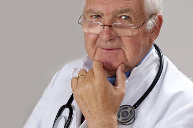 Starszy lekarz w białym fartuchu ze stetoskopem
