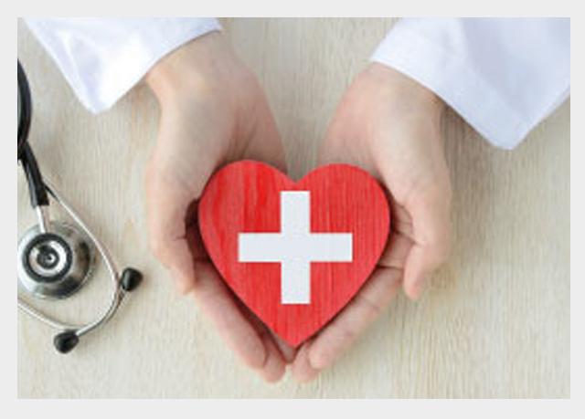 Dłonie lekarza trzymające drewniane czerwone serce z namalowanym po środku białym krzyżem