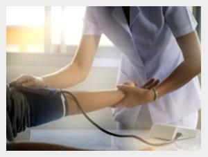Lekarka mierząca pacjentowi ciśnienie tętnicze