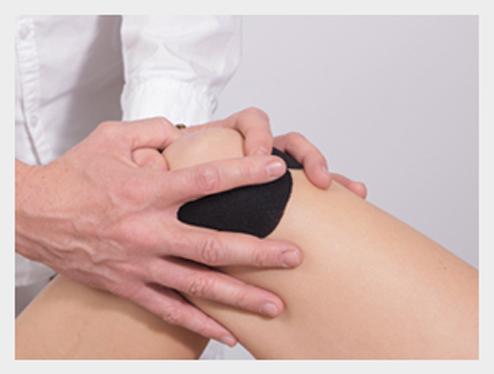 Lekarz zakłada na kolano pacjenta opaskę rehabilitacyjną